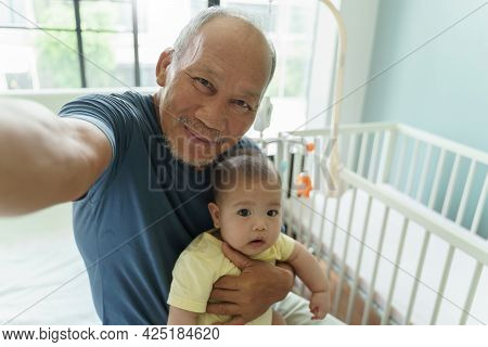 Cheerful Asian Grandparent And Little Cute Baby Boy Smiling Taking Selfie Photos With Smartphone At