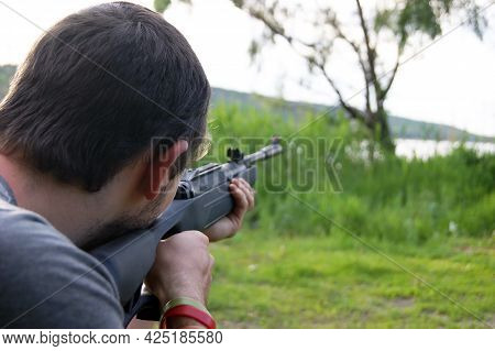 A Young Guy Is Preparing To Shoot From A Pneumatic Weapon.