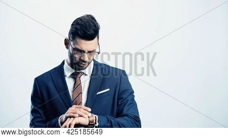 Young Businessman Checking Time On Wristwatch Isolated On White
