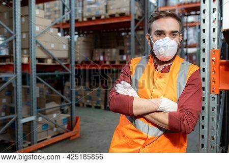 Worker in respirator and workwear crossing arms by chest