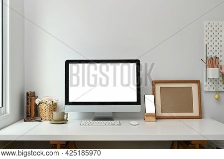 Workspace With White Screen Desktop Computer, Smart Phone And Stuff On White Table.