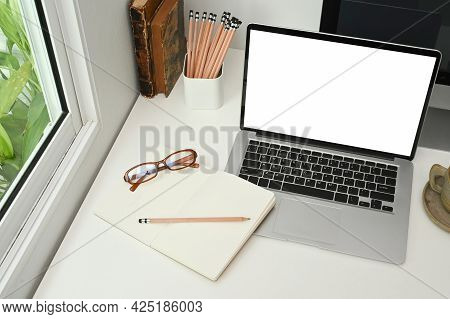 Photo Of Notebook, Pencils, Book And Computer Laptop With Empty Screen Are Putting Together On Worki