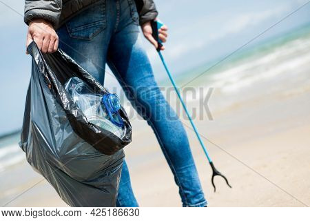 a man carries a gray bag full of waste, such as plastic containers and bottles, that he collects with a reach extender from the sand of a lonely beach, as an action to clean up the natural environment