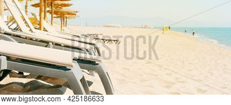 closeup of some beige sunloungers and some sun umbrellas on a quiet beach, in a panoramic format to use as web banner or header