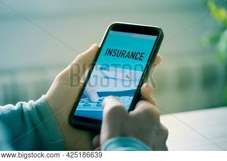a young caucasian man, sitting at a table, searches an insurance online with his smartphone, with a simulated search engine