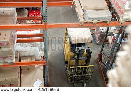 Cart moving along aisle between racks in large warehouse
