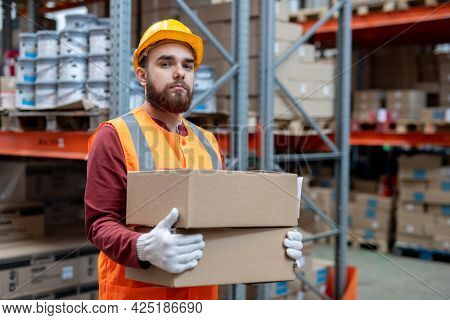 Gloved man in hardhat and workwear loading boxes with goods