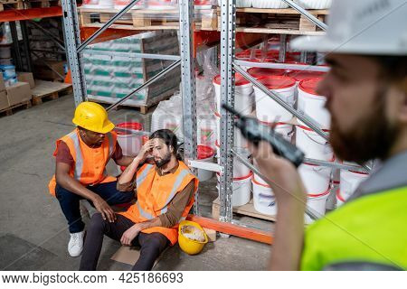 African man in workwear helping sick colleague with high temperature or headache