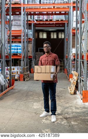 Young man of African ethnicity loading boxes with goods in storehouse
