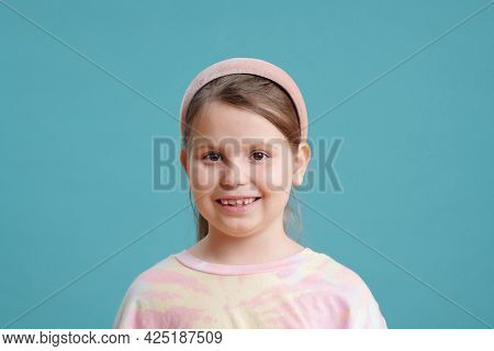 Cute little girl with toothy smile over blue background