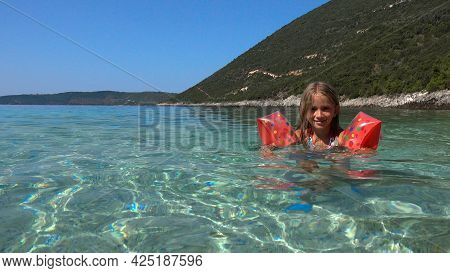 Kid Swimming In Sea Water On Beach, Child Playing On Seashore, Blonde Little Girl With Life Buoy Enj