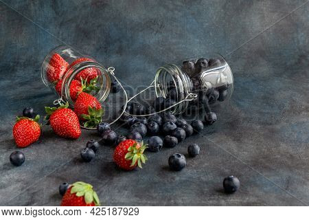 Blueberries And Strawberries In Glass Jars. Blurred Background. Rustic Style. Healthy Diet. High Qua