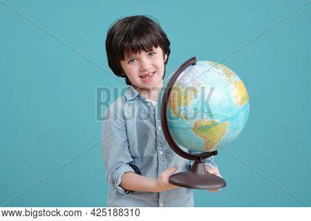 Adorable schoolboy or preschooler with globe looking at you