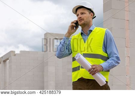Construction Engineer Supervisor Working At Building Site. Talking On The Phone