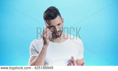 Discouraged Man Pointing At Himself With Finger While Talking On Smartphone Isolated On Blue