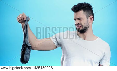 Displeased Man Grimacing While Holding Smelly Sock Isolated On Blue