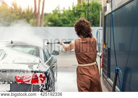 Back View Young Adult Woman Washing Car With High Pressure Water Equipment Pump Self-service Outdoor