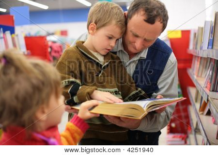 Grandfather And Grandson And Girl Read Book In Bookshop