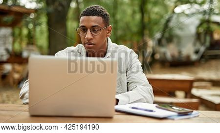 Young African American Freelancer Working On Laptop While Sitting At Wooden Table Outdoors, Widescre