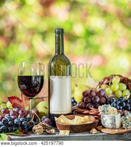 Grapes, bottle of wine and different cheeses on country wooden table and blurred colorful autumn background. Variety of products as the symbol of autumn abundance and prosperity.
