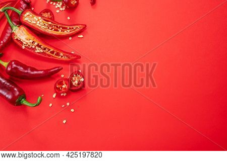 Fresh red chilli peppers  and peppers slices isolated on red background. Top view.
