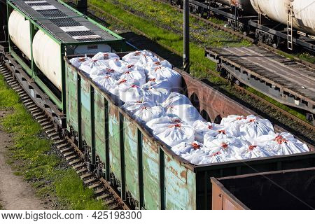 Transportation Of Fertilizers In Huge Bags And Wagons By Rail. Fertilizer Cars, Freight Train.
