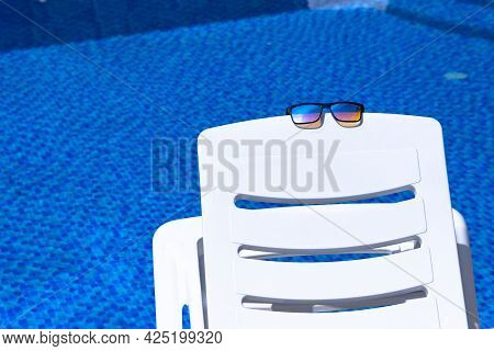 Sunglasses Lie On A White Chaise Lounge Against The Backdrop Of A Pool With Blue Water. Copy Space