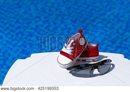 Sunglasses And Red Children's Gym Shoes Lie On A White Chaise Lounge Against The Backdrop Of A Pool
