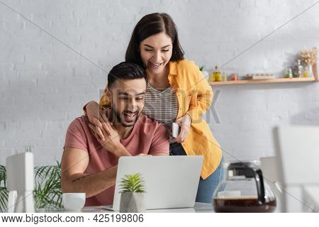 Smiling Young Woman Holding Cellphone And Touching Hands With Boyfriend Working With Laptop At Home