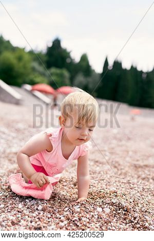 Little Girl With A Panama Hat In Her Hand Crawls Along A Pebble Beach