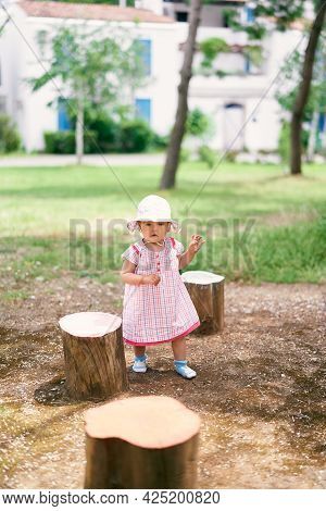 Little Girl In A Hat Stands Among The Stumps On The Background Of Buildings