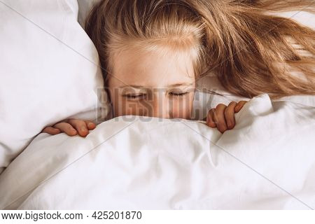 Child Hiding Under Duvet In Bed. The Girl Closed Her Eyes Under The Covers