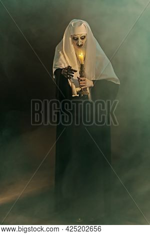 Full length portrait of a scary devilish possessed nun with a candle in her hands standing in a dark room in smoke. Horrors and Halloween.