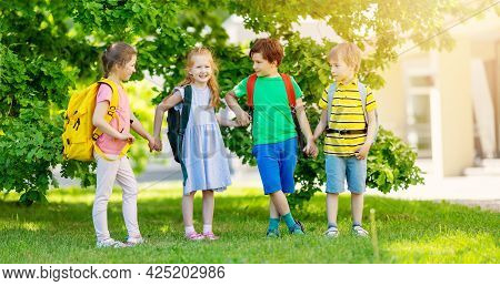Cute Children With Rucksacks Standing In The Park Near The School