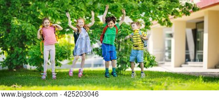 Cute Children With Rucksacks Jumping And Playing In The Park Near The School