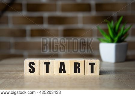 Start Now Or Later Symbol. Wooden Cubes And Changes Words Start. Beautiful Background, Copy Space. B