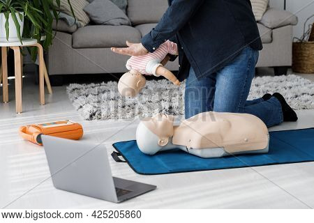 Paramedic Demonstrating First Aid On Manikin During Training Alone In Living Room