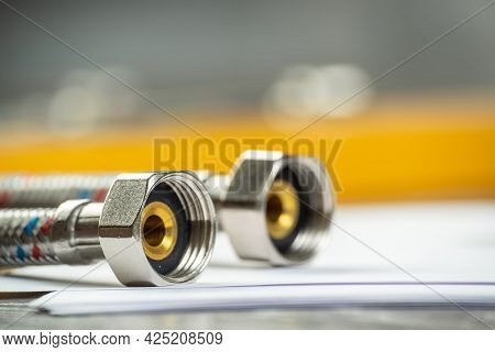 Flexible Steel Water Hoses Laying On Table. Close Up Water Fittings And Connections With Segments Of