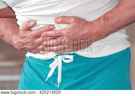 Hands Of A Man Holding His Stomach, Suffering From Pain, Diarrhea, Digestive Problems