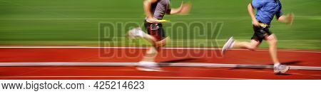 Motion blurred image of  track and field runners in a relay race