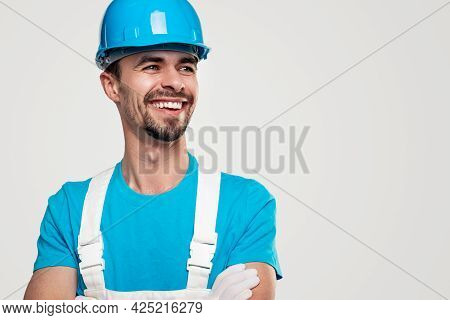 Positive Bearded Male Contractor In Workwear And Hardhat Crossing Arms And Looking Away With Confide