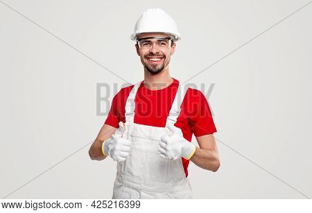Delighted Man In Uniform And Goggles Smiling And Showing Thumb Up Gesture While Approving Constructi