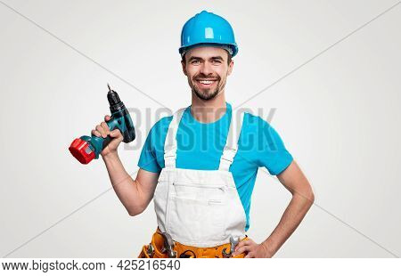 Confident Positive Repairman In Blue Shirt And Hardhat And White Overall With Toolkit On Waist And E
