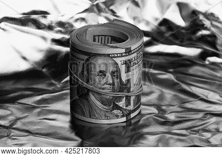 Roll Of One Hundred American Dollars Close-up Black And White Style. A Big Pile Of Cash Dollars. One