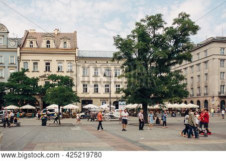 Krakow, Poland - July 21, 2019: Town Houses At Main Square With Tourists Walking In Old Town, Popula