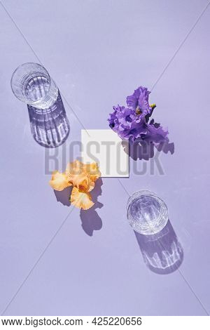 Two Glasse With Water And Card Note With Iris Flowers On Pastel Lilac Background. Summer Refreshment