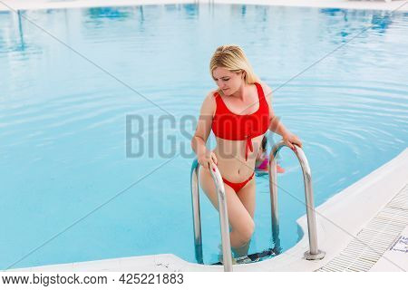 Woman Enjoying Vacation Holidays At Luxurious Beachfront Hotel Resort With Swimming Pool And Tropica