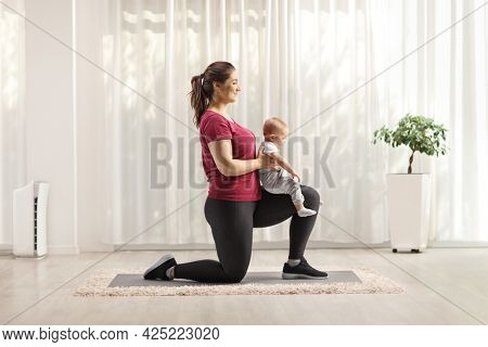 Young mother kneeling, exercising and holding a baby indoors