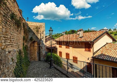 Narrow cobblestone street with lamppost among old surrounding wall and houses under beautiful sky in small town of Monforte d'Alba, Piedmont, Northern Italy.