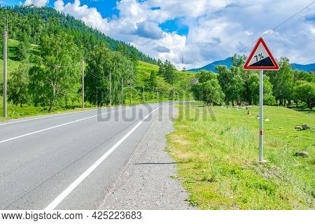 A Road Sign, A Symbol For Car Drivers, Warning About Climbing Uphill On An Asphalt Road, On A Highwa